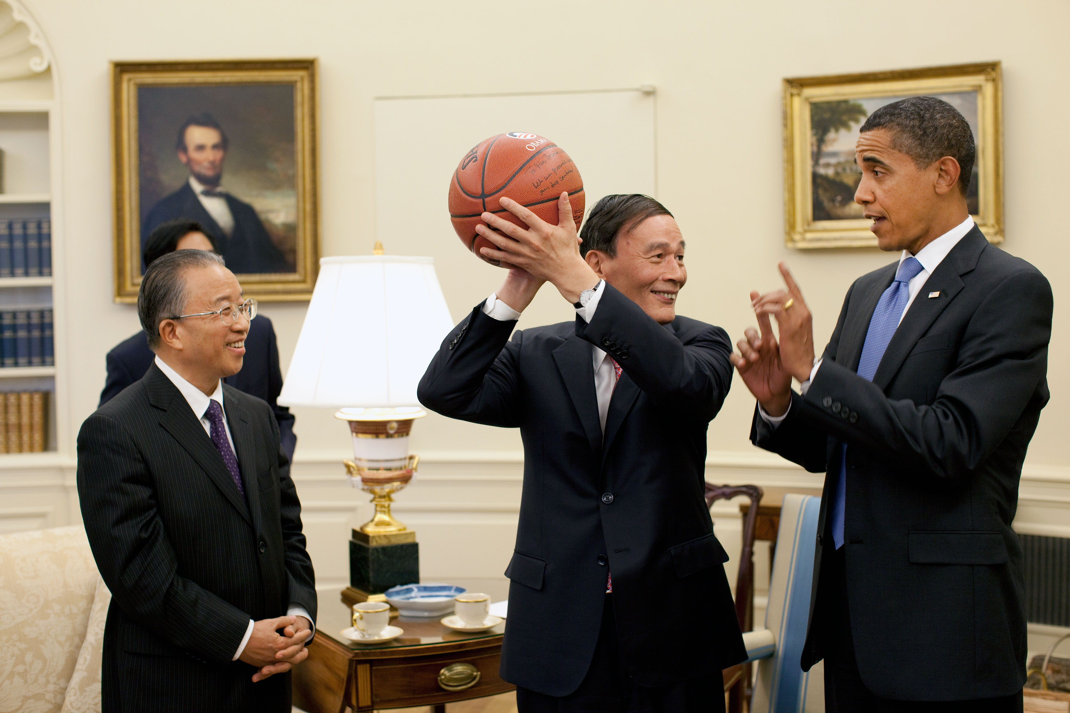 Chinese Vice Premier Wang Qishan, center, holds the basketball given to him by President Barack Obama following their Oval Office meeting Tuesday, July 28, 2009, to discuss the outcomes of the first U.S.-China Strategic and Economic Dialogue.  Looking on at left is Chinese State Councilor Dai Bingguo. (Official White House Photo by Pete Souza)